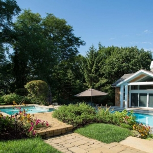 small pool house with cedar shake siding and white trim. Paver patio. Hot tub. In ground pool. Poolside seating and umbrella.