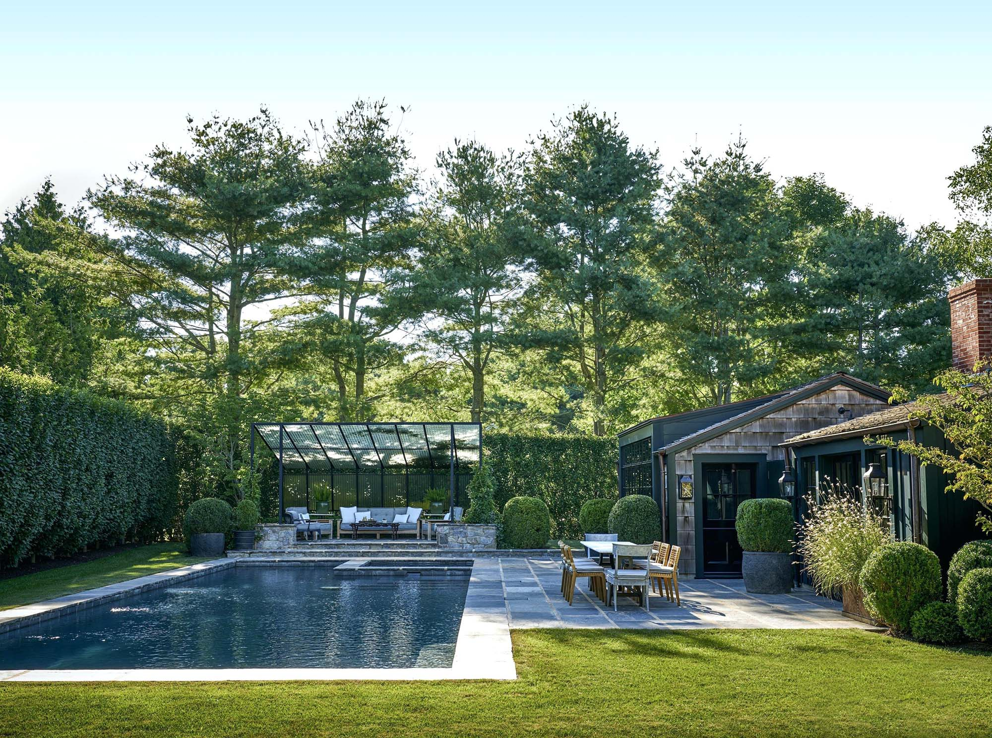 rustic pool house design in gound rectangle concrete pool with blue stone patio real stone seating area