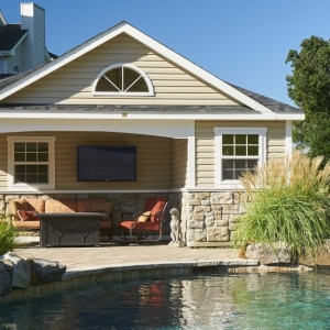 cute pool house design real stone pooside landscaping hardscaping red cushions wall hung TV