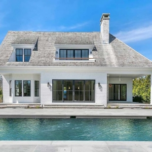modern white pool house design blue stone patio black frame windows brick chimney