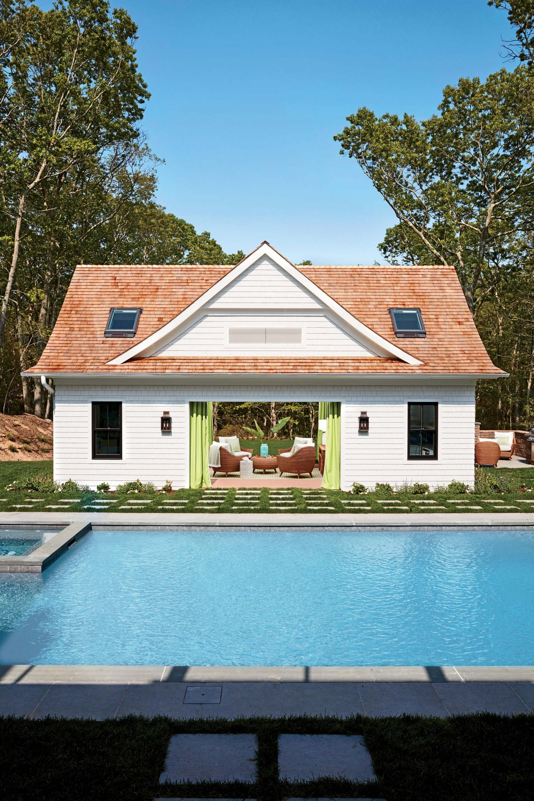 cute pool house design open french doors white siding green curtains stone tile