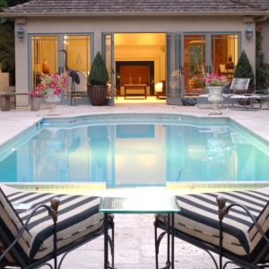 stucco pool house with gray french doors