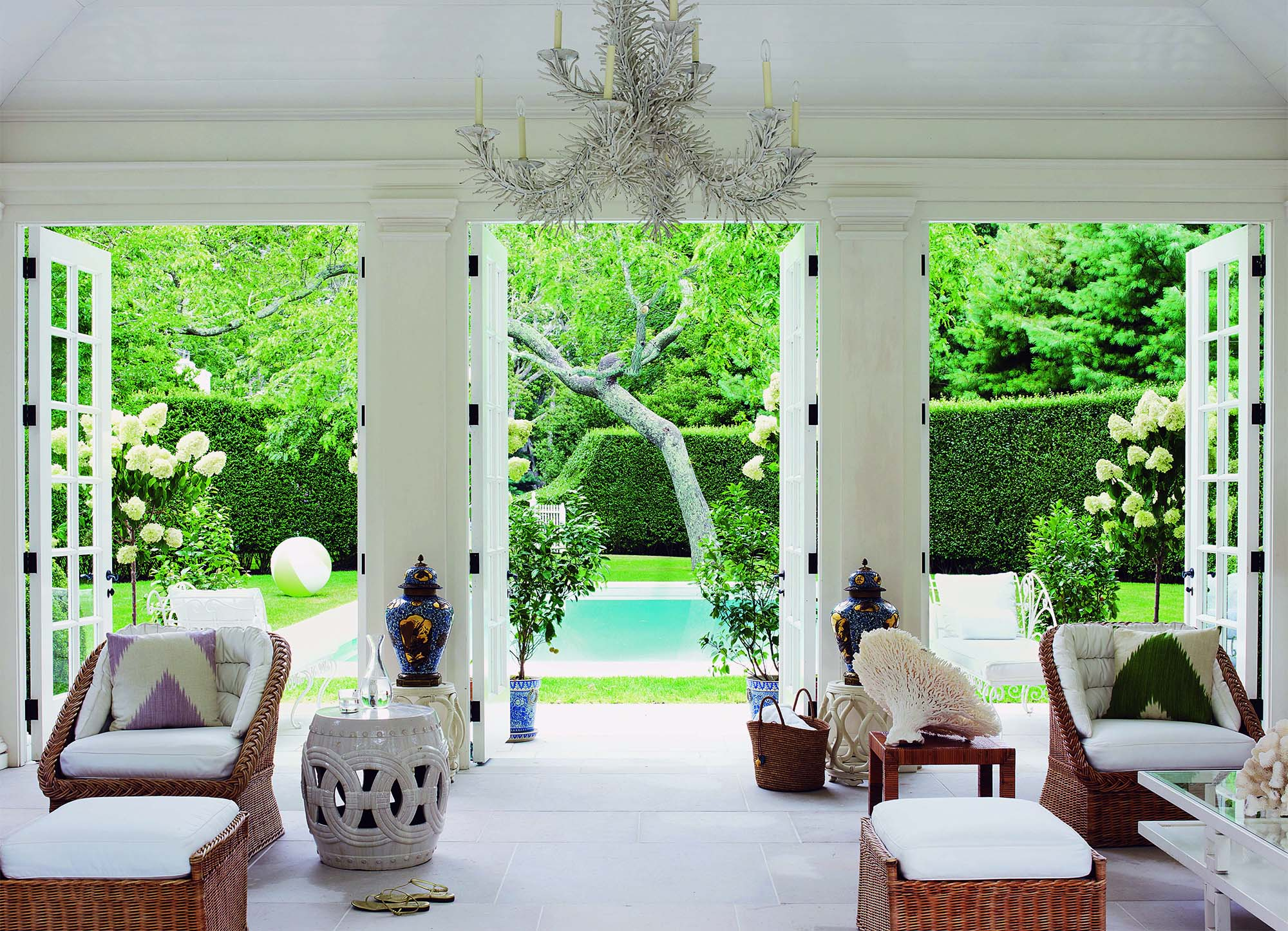 pool house interior french doors stone floors light and bright wicker furniture white cushions