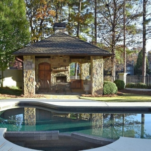 Beautiful small pool house design with real stone veneer siding. Real wood doors and an outdoor fireplace. Concrete patio surround. In ground pool.