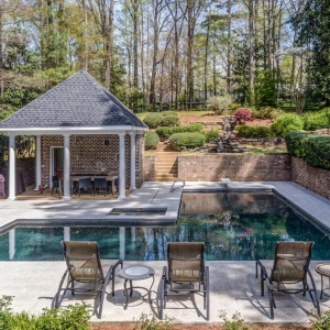 Small pool house design with red brick walls and a black shingle roof. Concrete patio. Rectangle in ground pool. Covered seating area. Red brick retaining walls. Poolside seating.