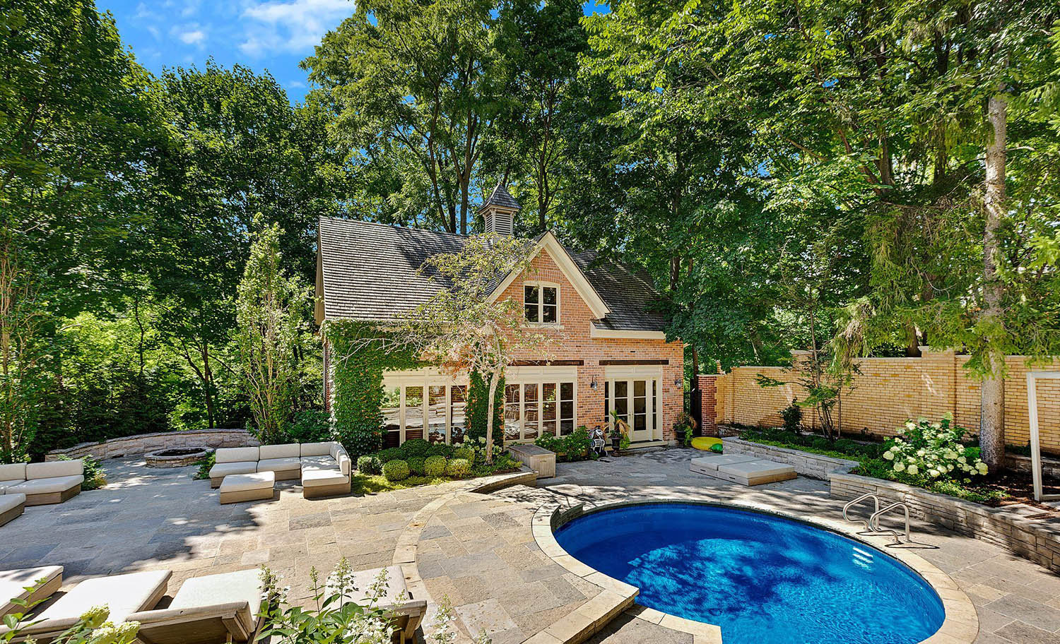 Large pool house design with red brick walls and tan trim. Wall ivy. Round in ground spa pool. Large stone patio with seating poolside.