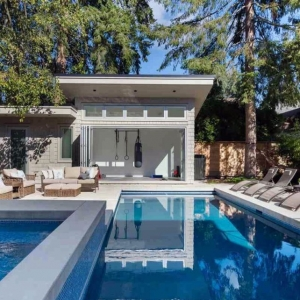 Modern pool house design. Rectangle in ground pool with hot tub. Pool side furniture. Wicker chairs with white cushions. Workout home gym. Folding glass patio doors. Flat roof.