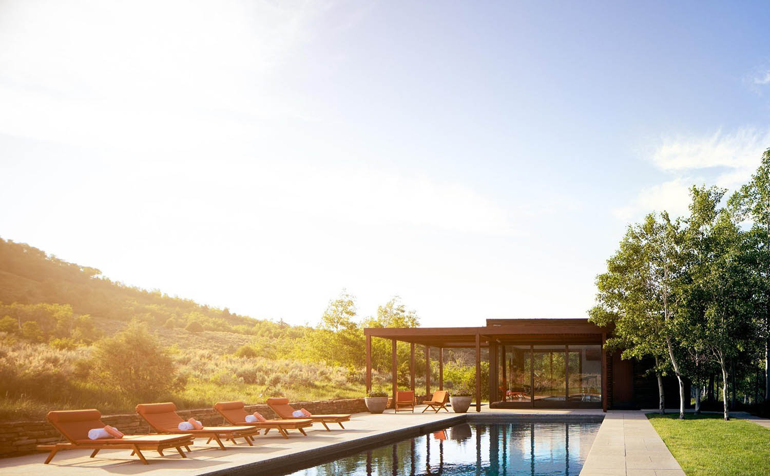 Beautiful modern pool house design in the country at sunrise. Huge floor to ceiling windows. Metal and wood siding. In ground rectangle pool. Poolside seating. Stone retaining walls. Flat roof.