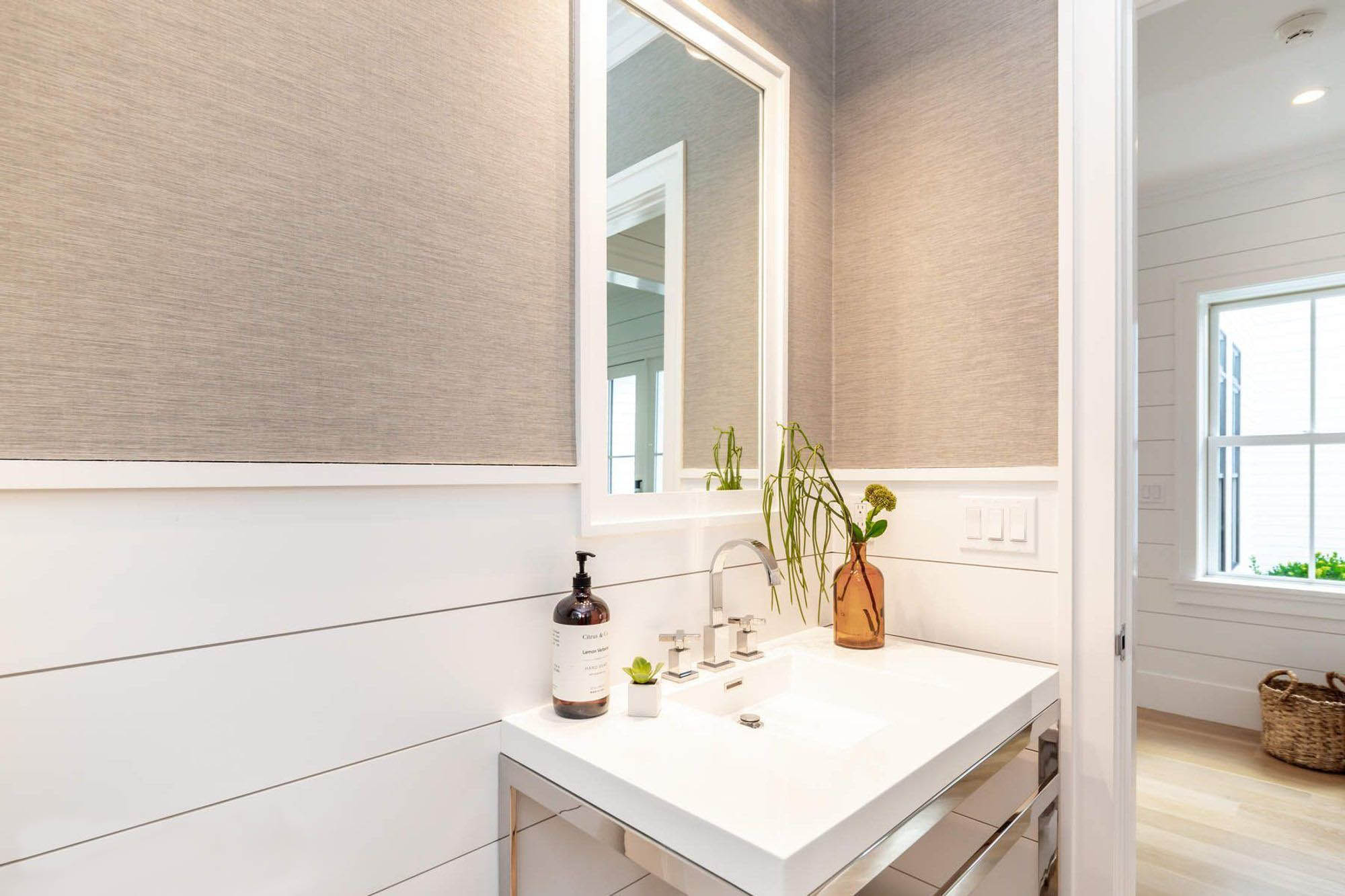 Bathroom shiplap wainscoting wall paneling with warm gray textured wallpaper. White sink with chrome faucet and vanity stand.