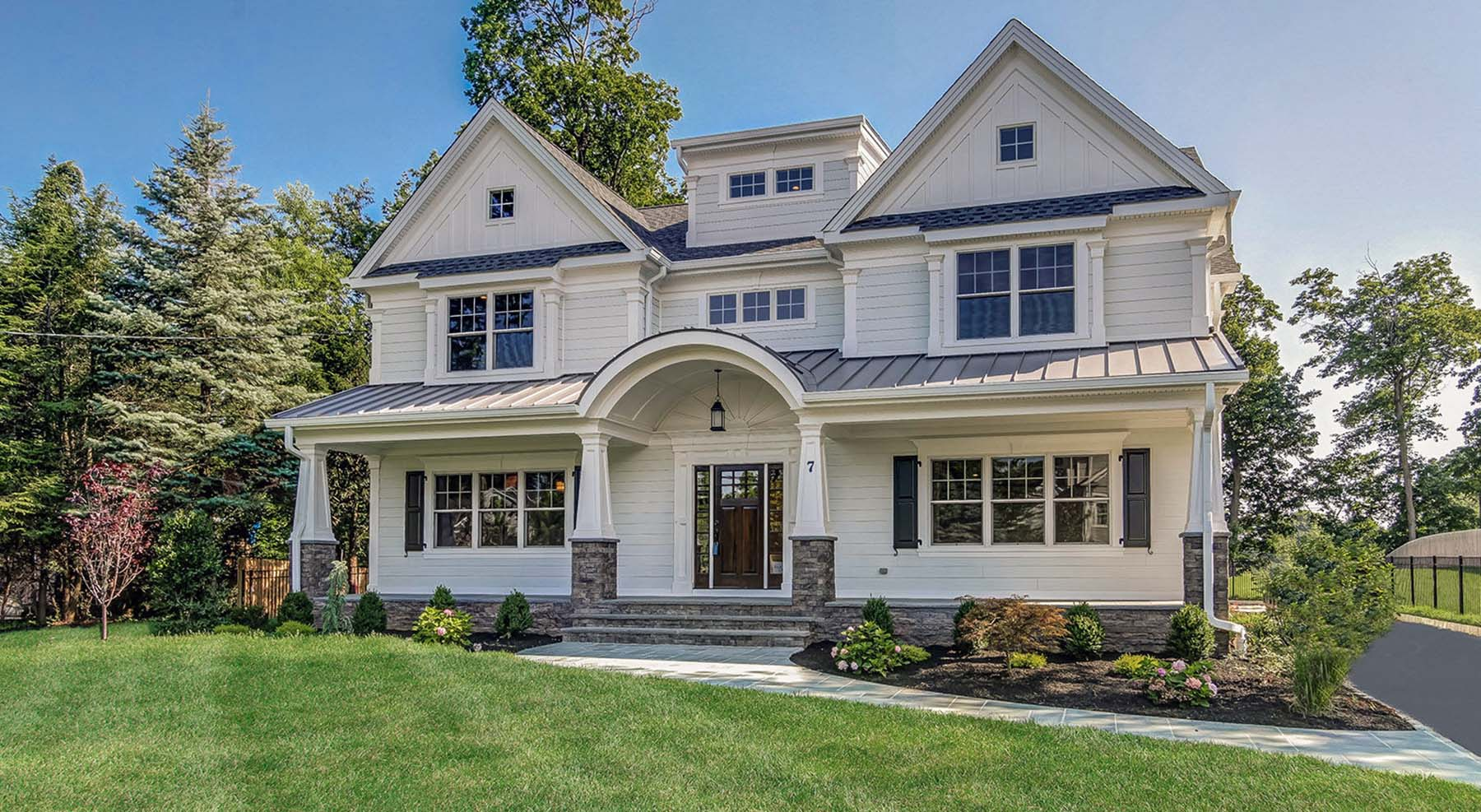 white lap siding with stone veneer base metal roofing arched front door