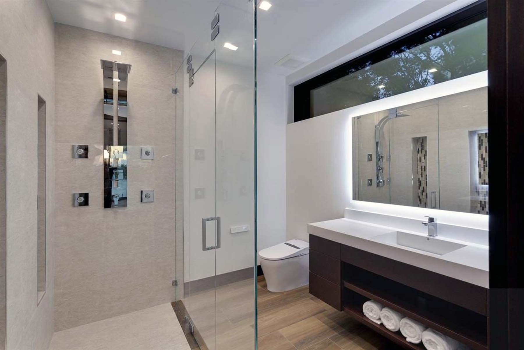 Modern bathroom with faux wood floor tiles, dark wood cabinetry and marble.