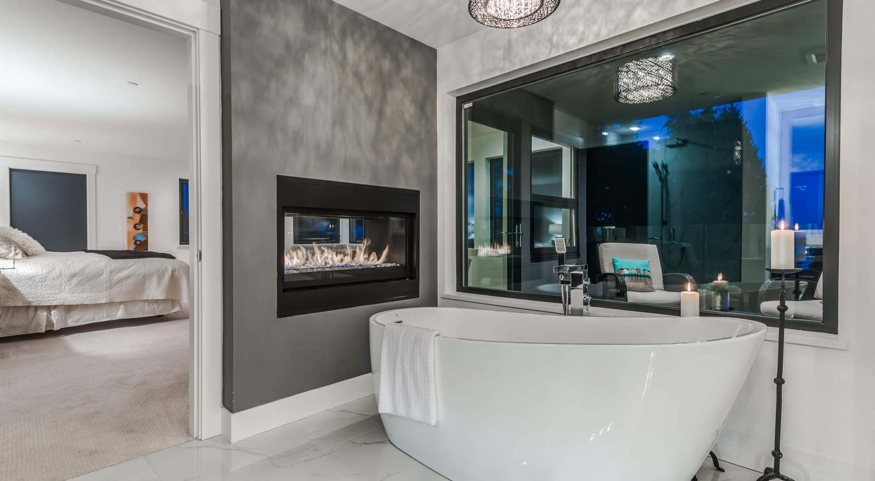 Modern master bathroom with built in double sided gas fireplace next to a free standing tub.