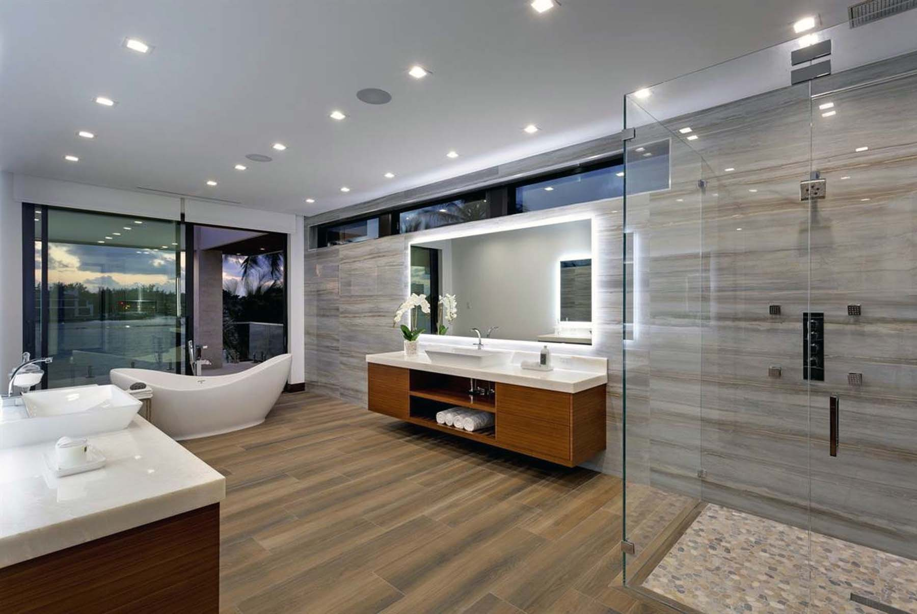 Modern bathroom design with large open floor plan and glass enclosed shower. White soaking tub.
