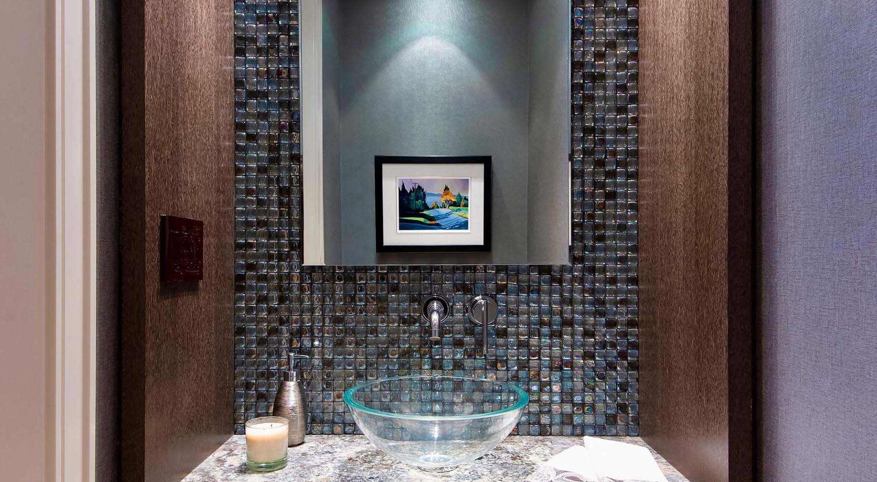 Glass tile backsplash in this modern bathroom design. Glass is a common material used in contemporary design.