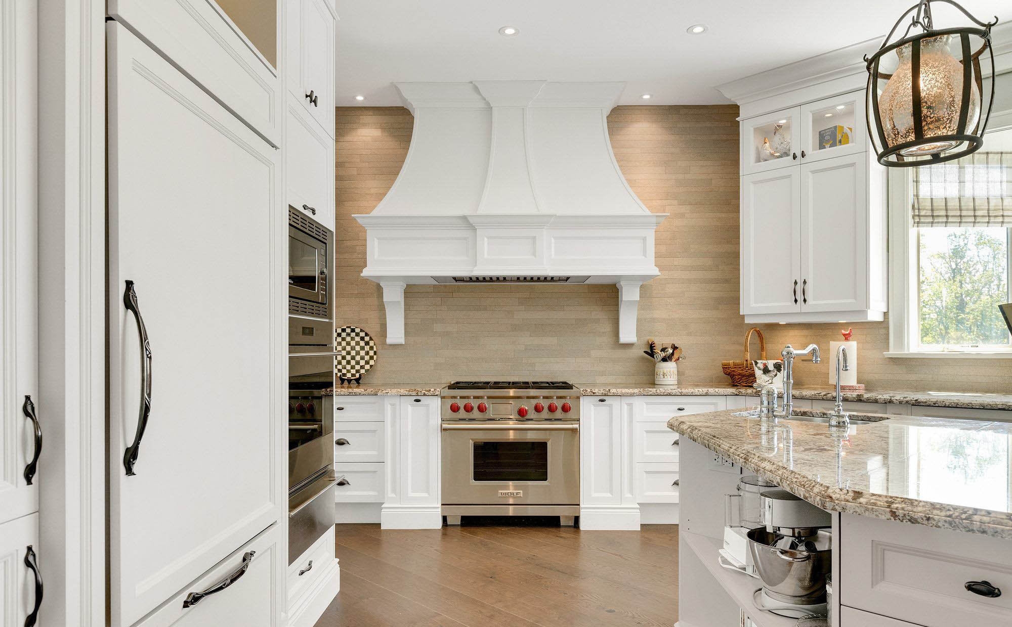 "36"" Wolf range in a beautiful luxury kitchen. Wood floors with white cabinets, stone countertops and tan stone backsplash."