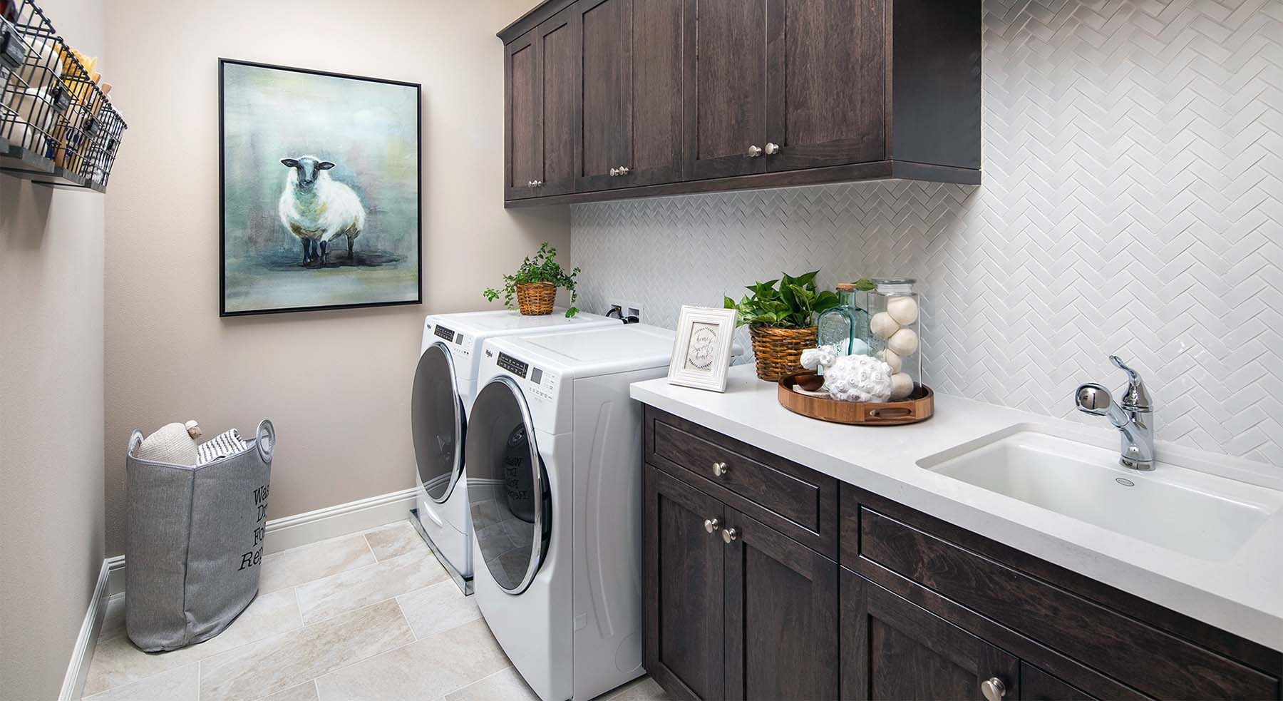beautiful laundry room white front loaders with dark brown cabinets white countertop and backsplash