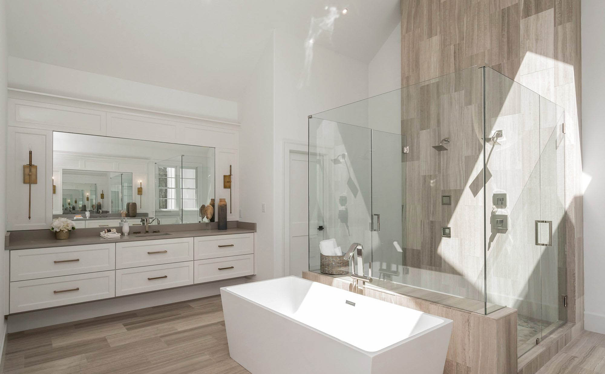 modern bathroom design. gray and white design. shaker style cabinets. tile walls. glass shower. soaking tub.