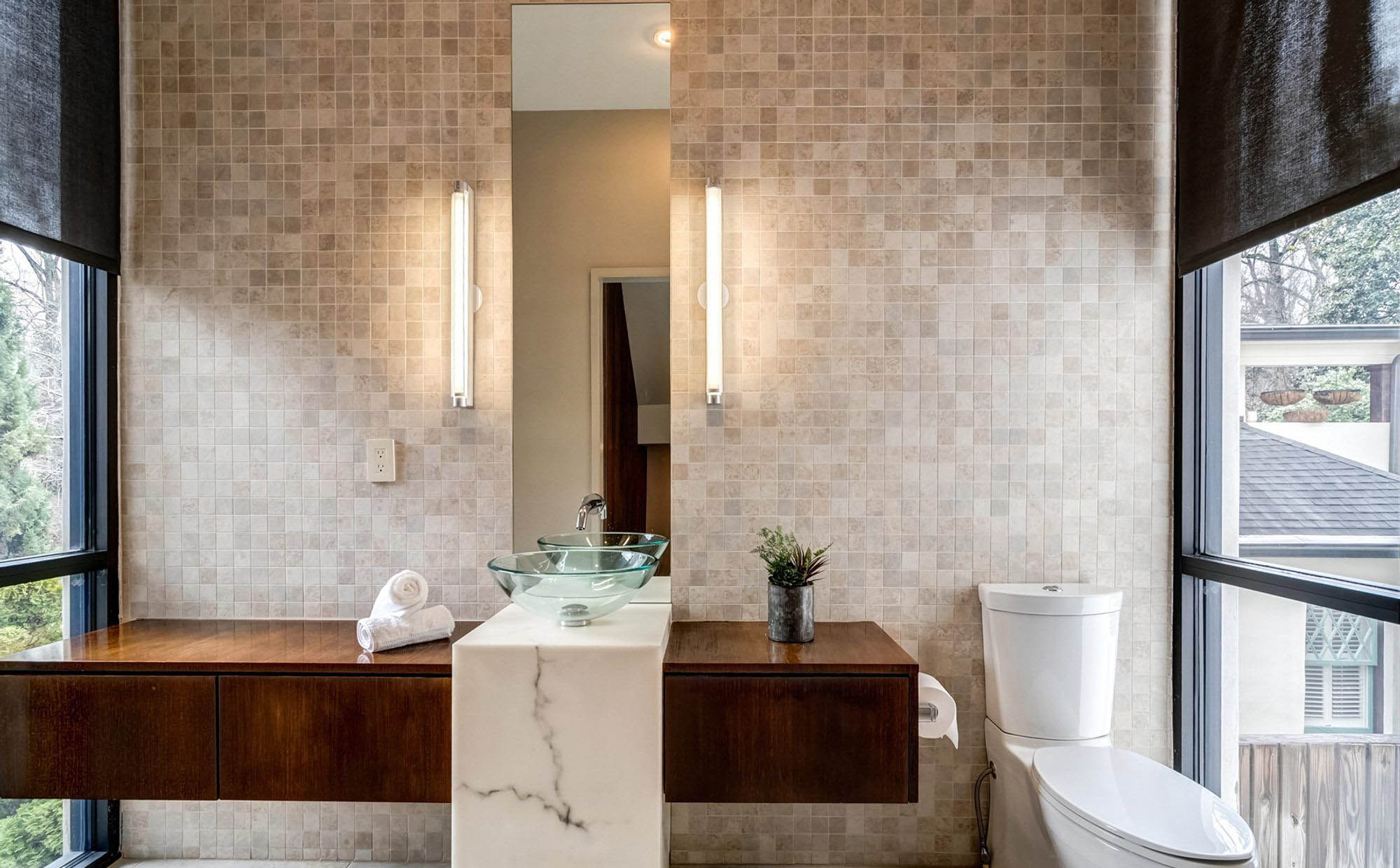 Modern bathroom with vertical wall sconces aside a tall thin mirror, marble and wood cabinetry with glass bowl sink.