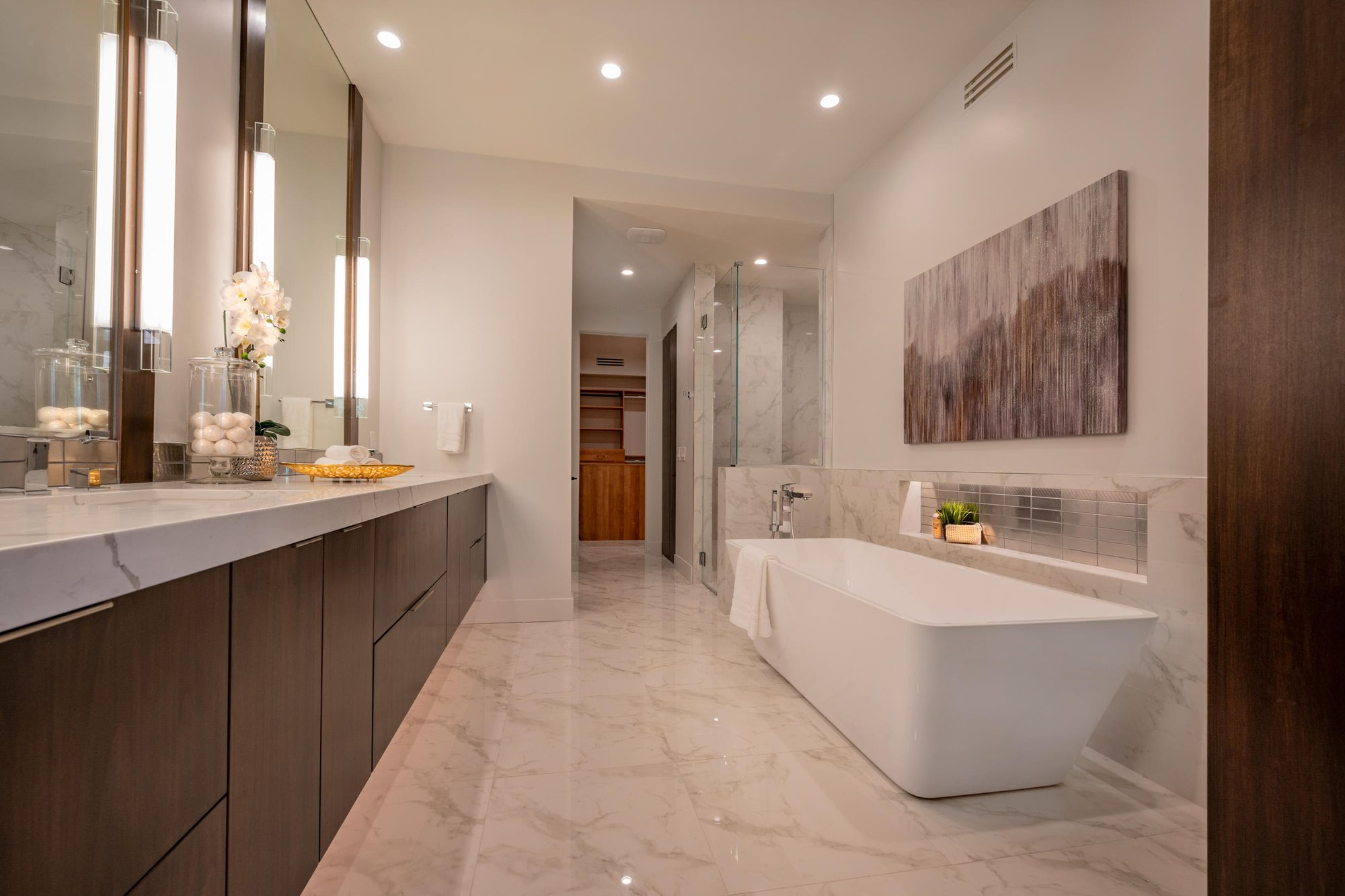 Beautiful modern master bathroom with warm undertones. Real wood with marble. White soaking tub.