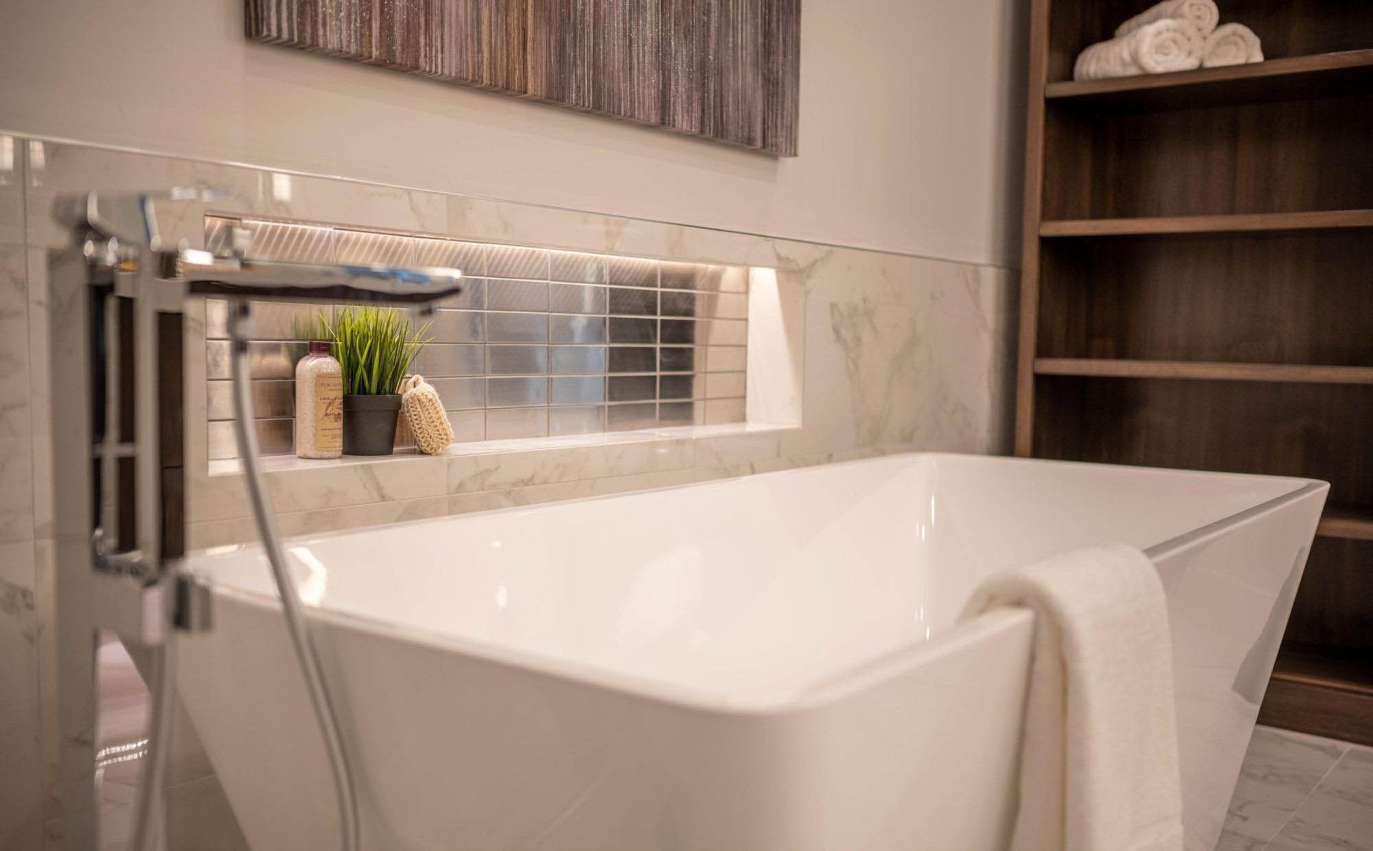 Modern creamy white soaking tub with built in shelf. Metallic backsplash tile matches the chrome faucet stack. The room has a warm undertone throughout.
