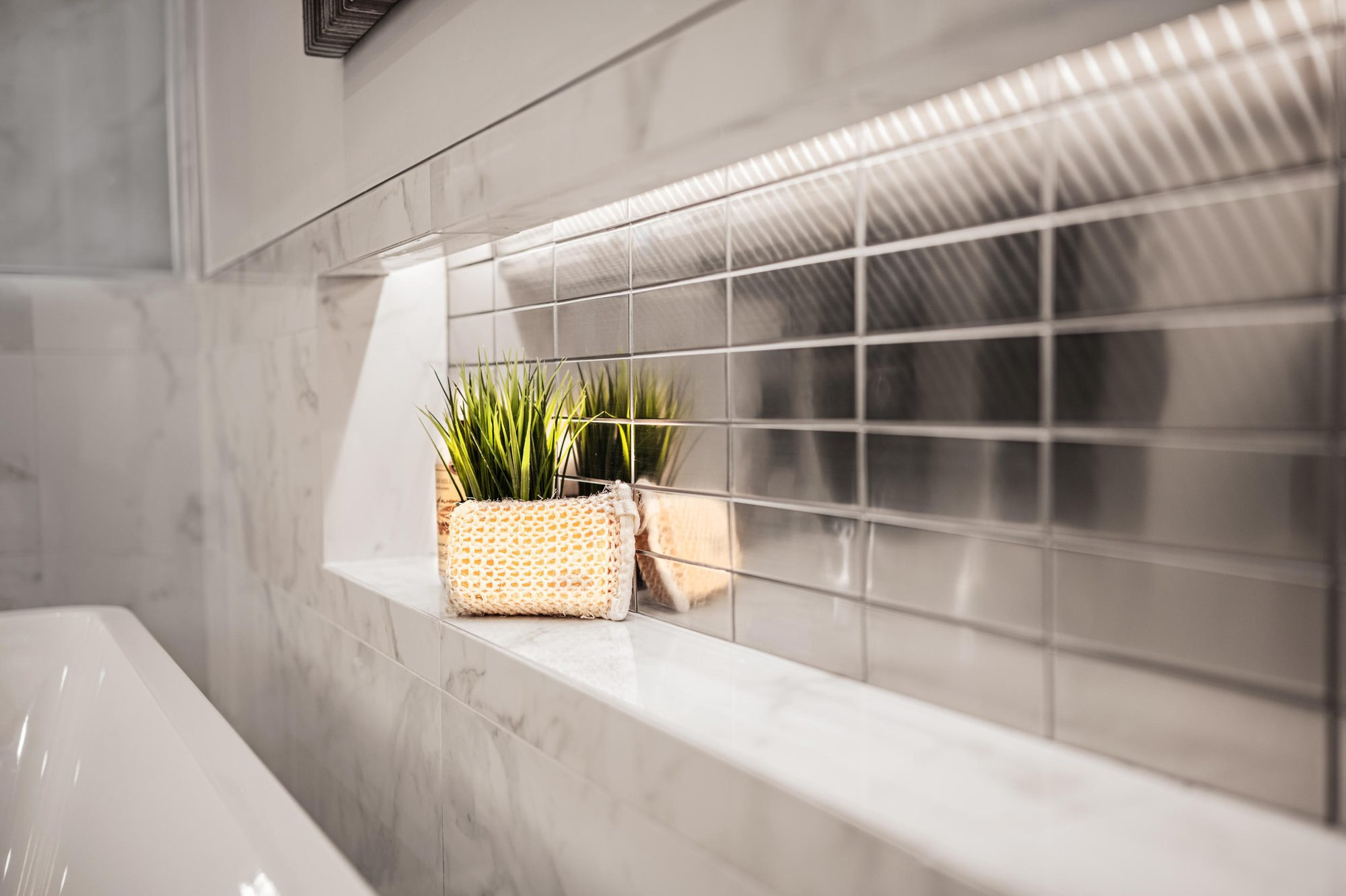 Small details matter in an ultra modern bathroom design. Simple minimalist choices tend to work best. Clean tub shelf with marble and silver metallic backsplash tiles.