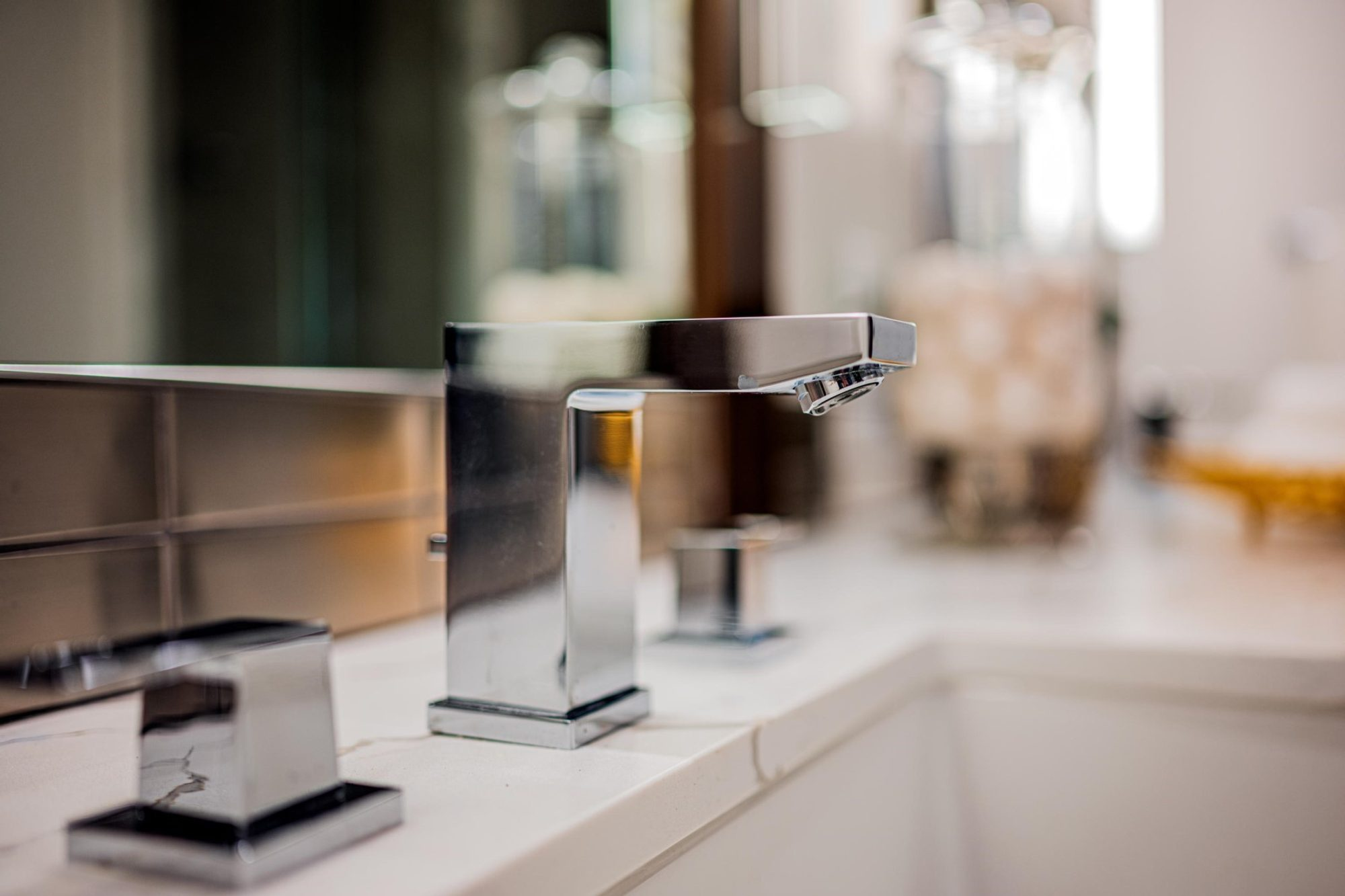 Closeup of a beautiful modern chrome bathroom faucet. Simple, clean, crisp design with square edges.