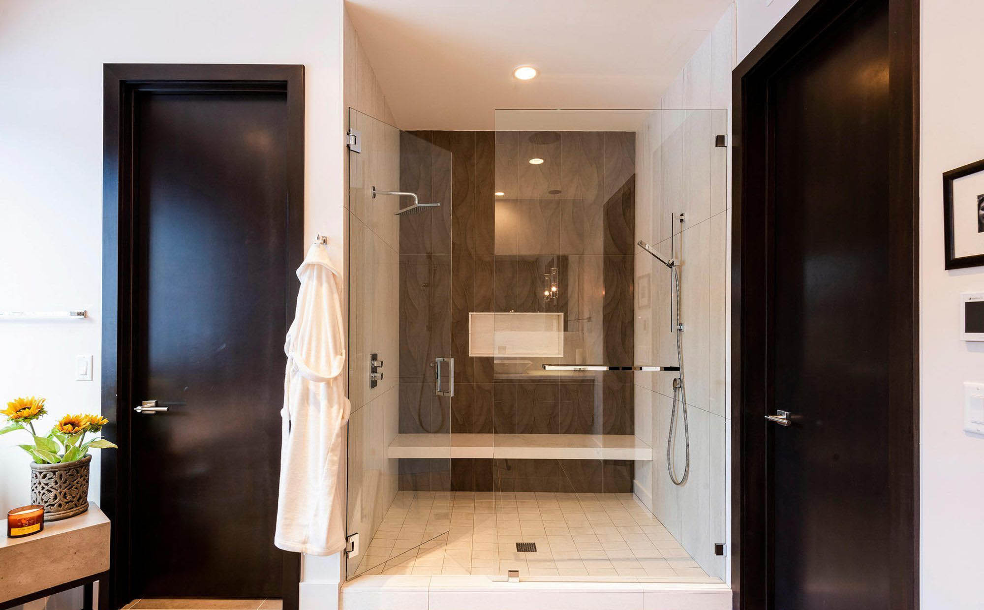 modern master bathroom standup shower with bench seat double shower heads glass doors cream and brown tiles