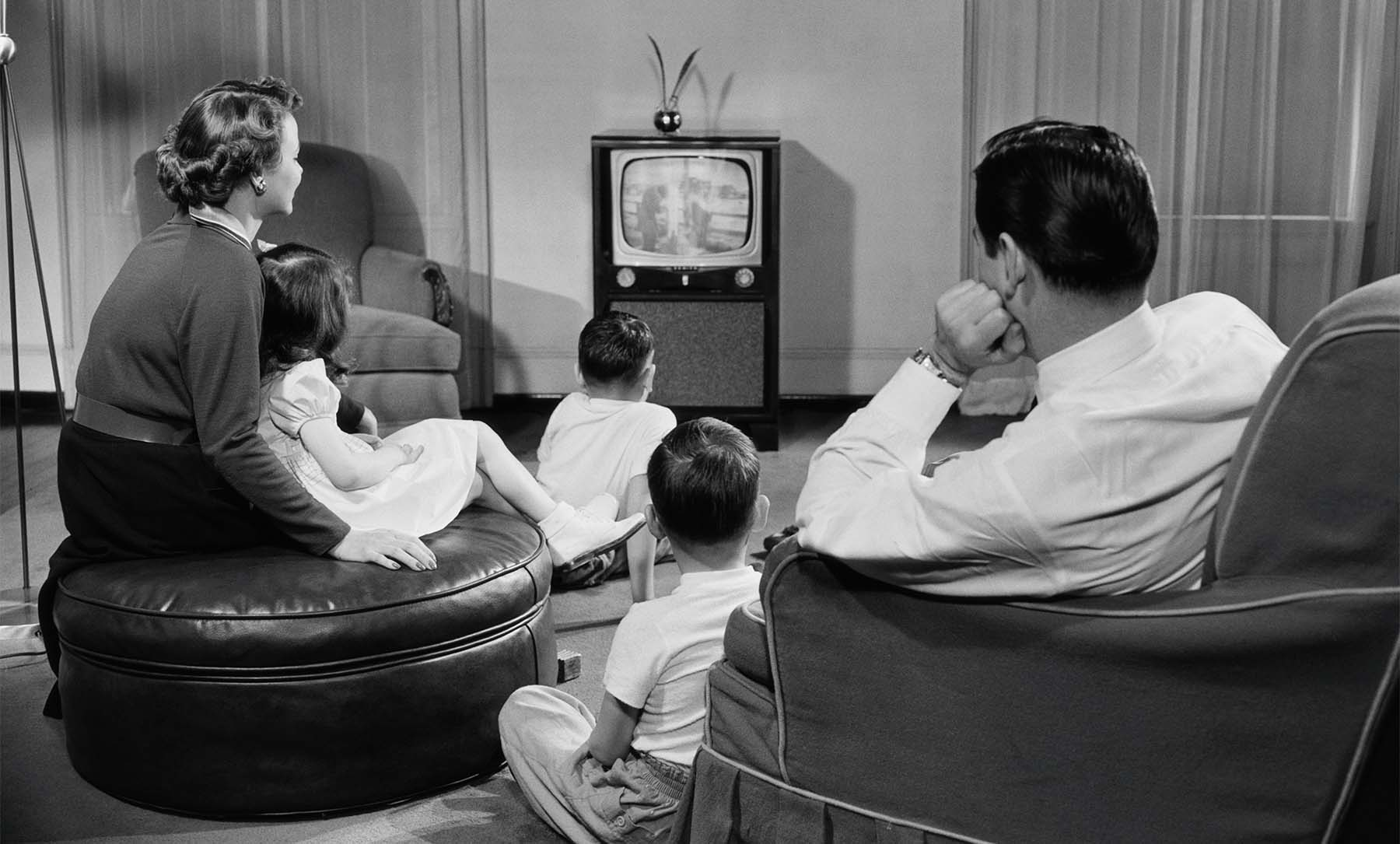 old fashioned black and white photo of family watching tv