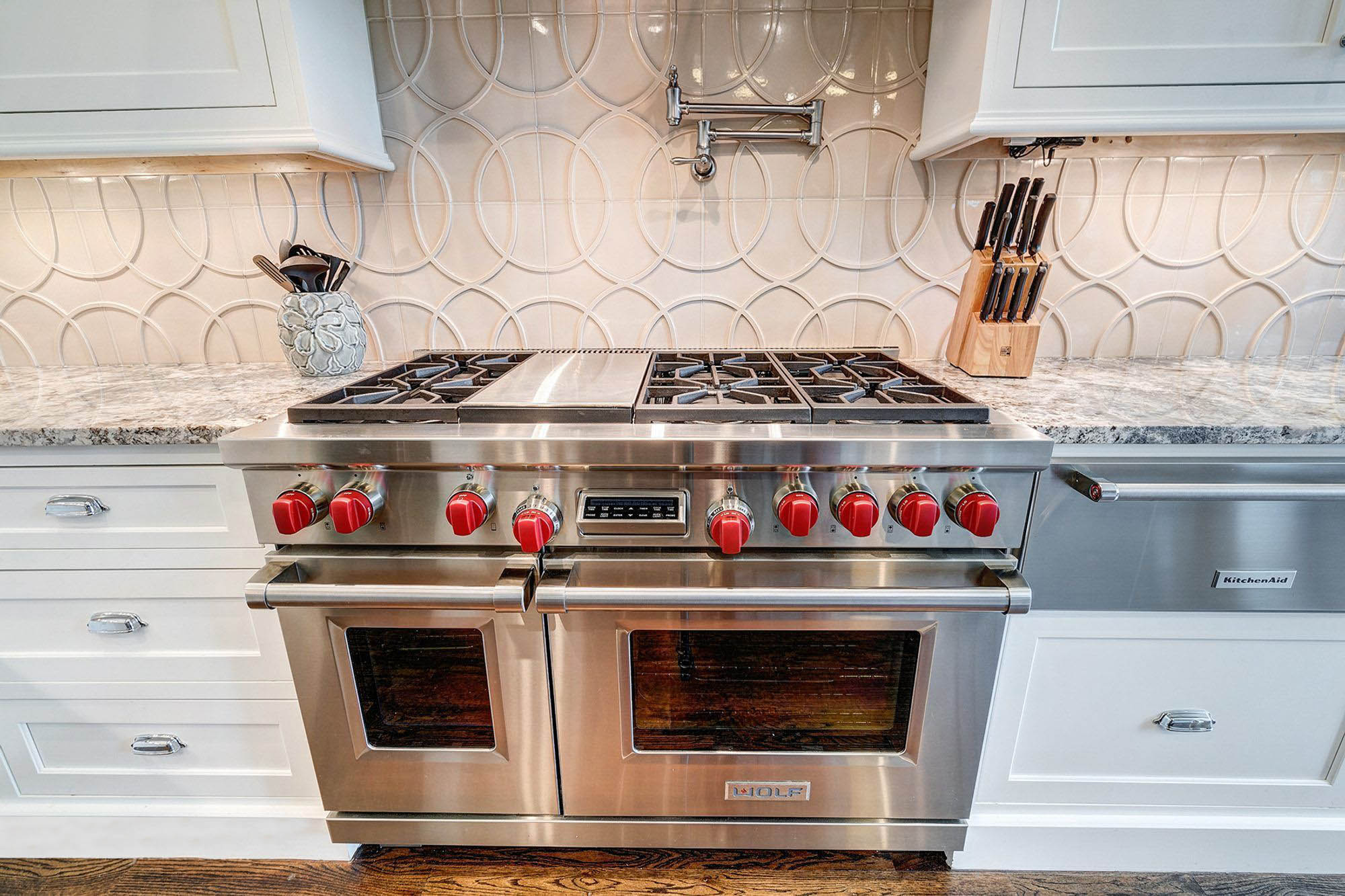 "48"" Wolf range with dual ovens, stainless steel finish and red knobs. Viking vs Wolf ranges"