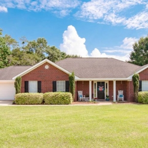 Red brick ranch style home with brown gray roof shingle color. Black front door with black shutters. White garage door. White trim and columns.
