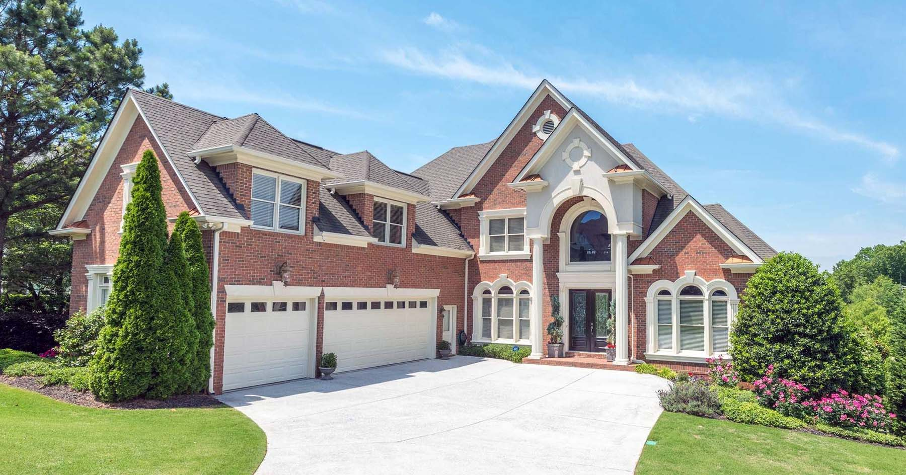 Red brick home with brown gray roof shingle color. Black french style front door. White garage doors. Stone and stucco columns and siding accents. Brown metal roof accents.