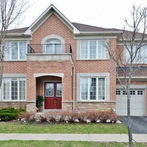 Red brick home with brown shingle roof color, tan stone trim, black metal railings. Taupe garage doors. Real stone veneer. Reddish brown front door.
