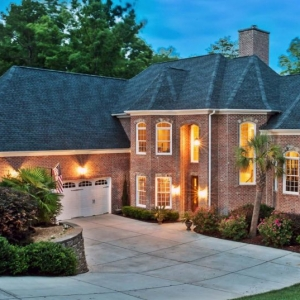 Beautiful red brick home with black asphalt shingle roof. White trim with white garage doors. Real wood front door. Dormer with stone veneer.