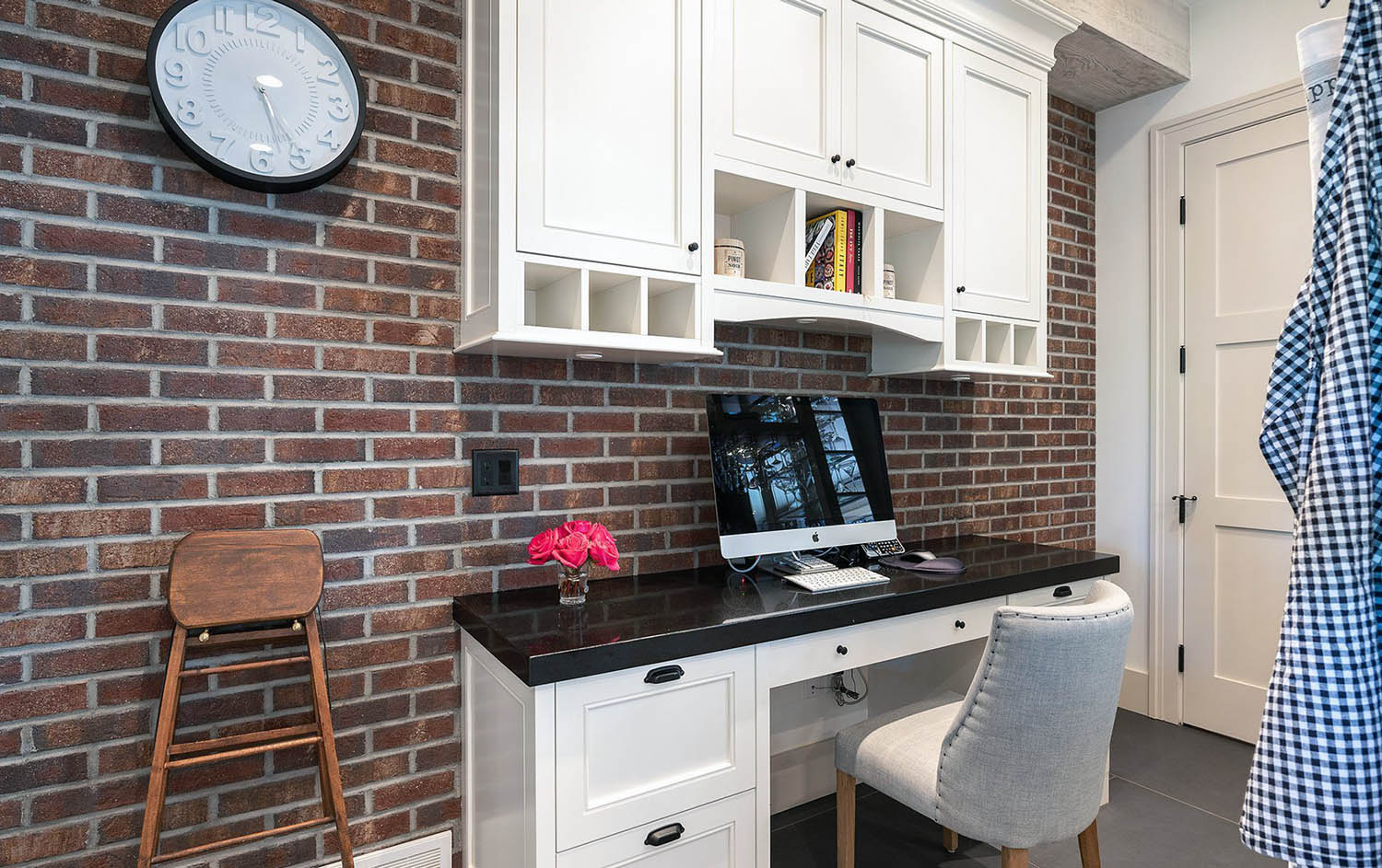 red brick home office accent wall with white wall pant and desk.
