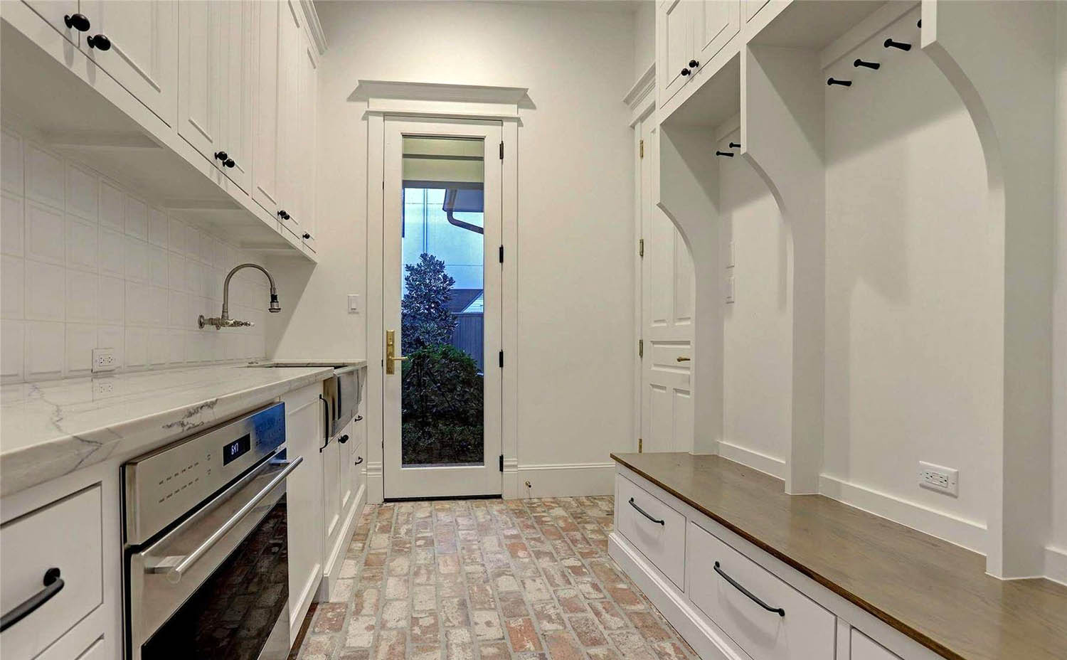 prep kitchen with red brick floor and whote walls marble countertops built in seating and storage