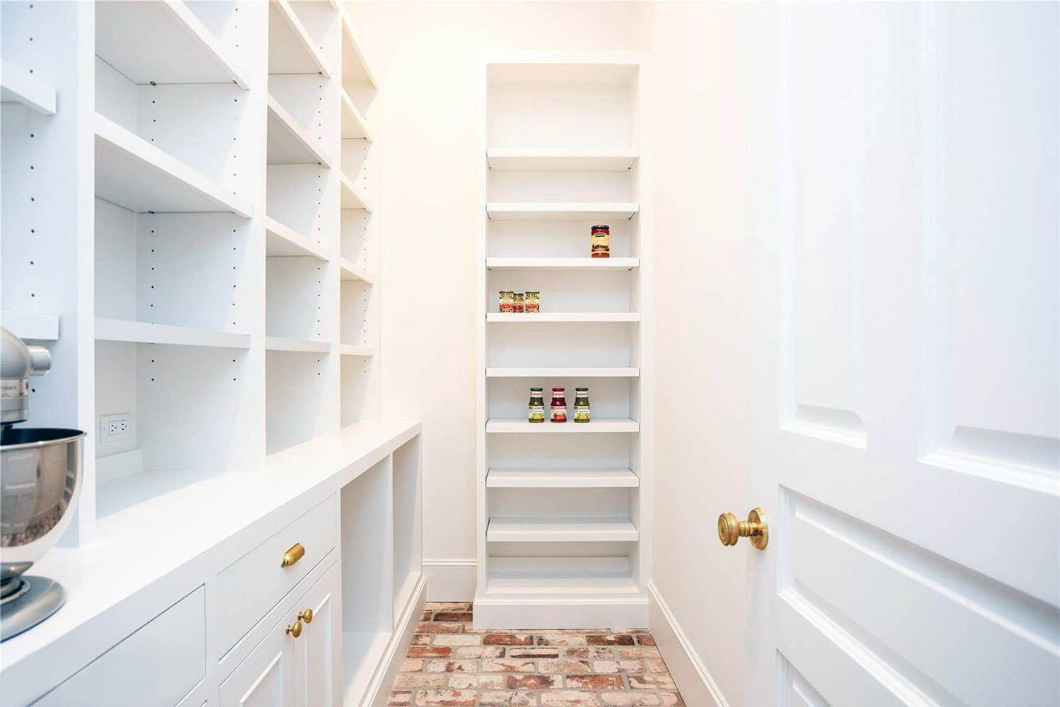 Red Brick Pantry Floor With White Walls lots of white cabinet storage gold hardware