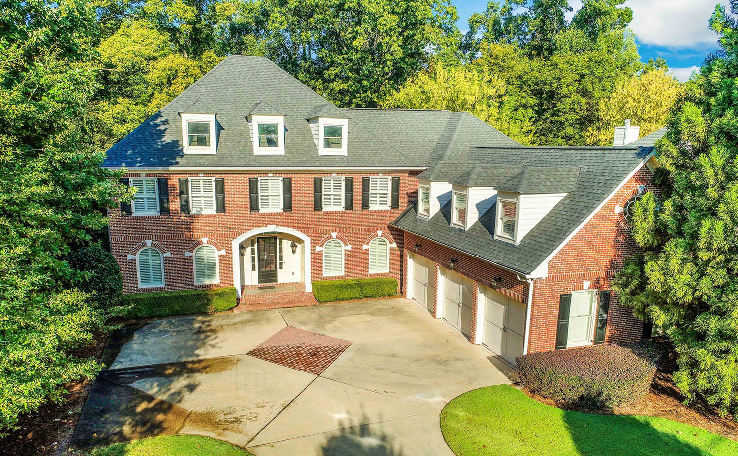 Beautiful red brick home with light tan garage doors and matching trim. Black front door and shutters.