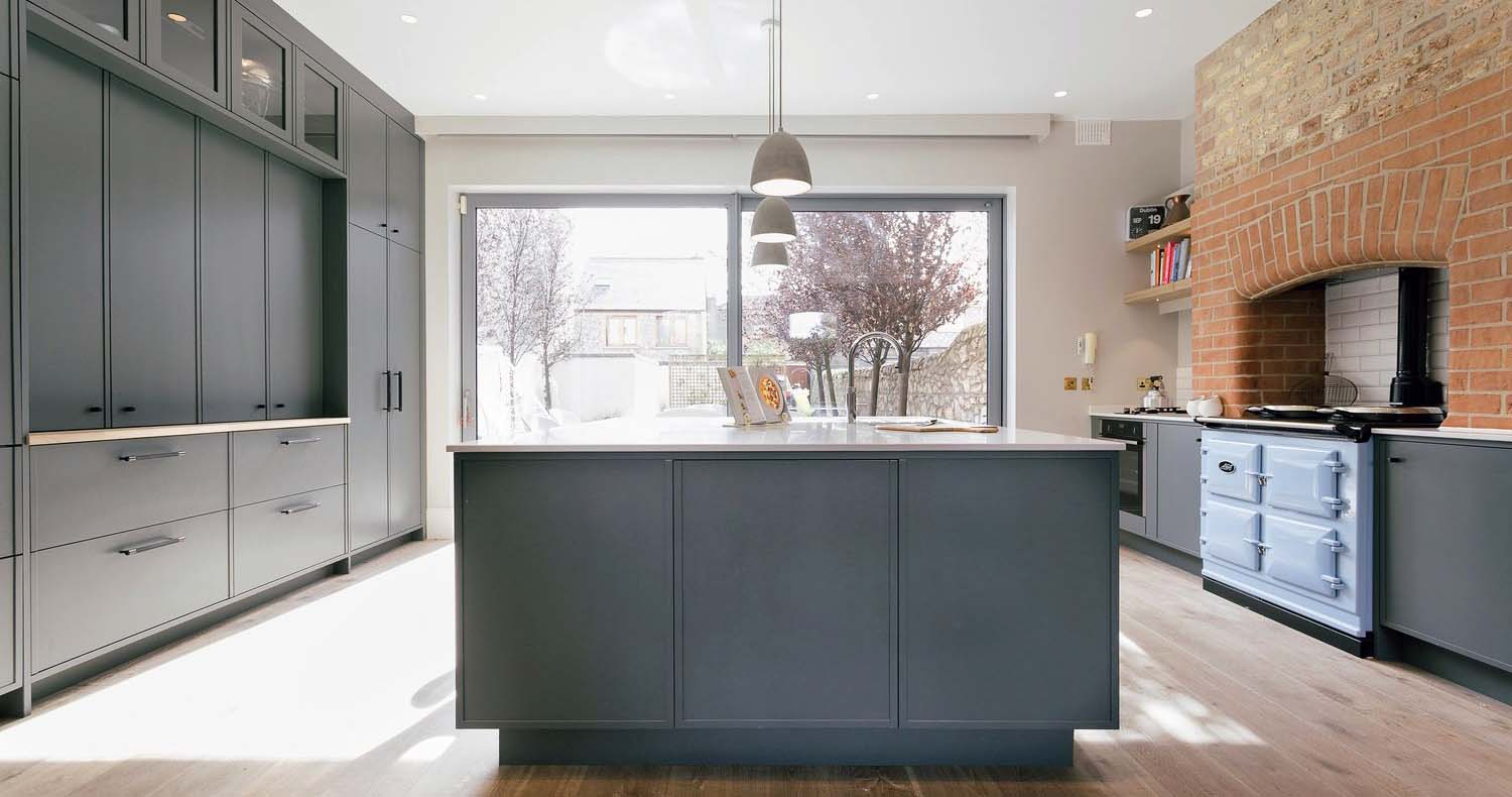 red brick kitchen chimney with exposed stove pipes gray cabinets