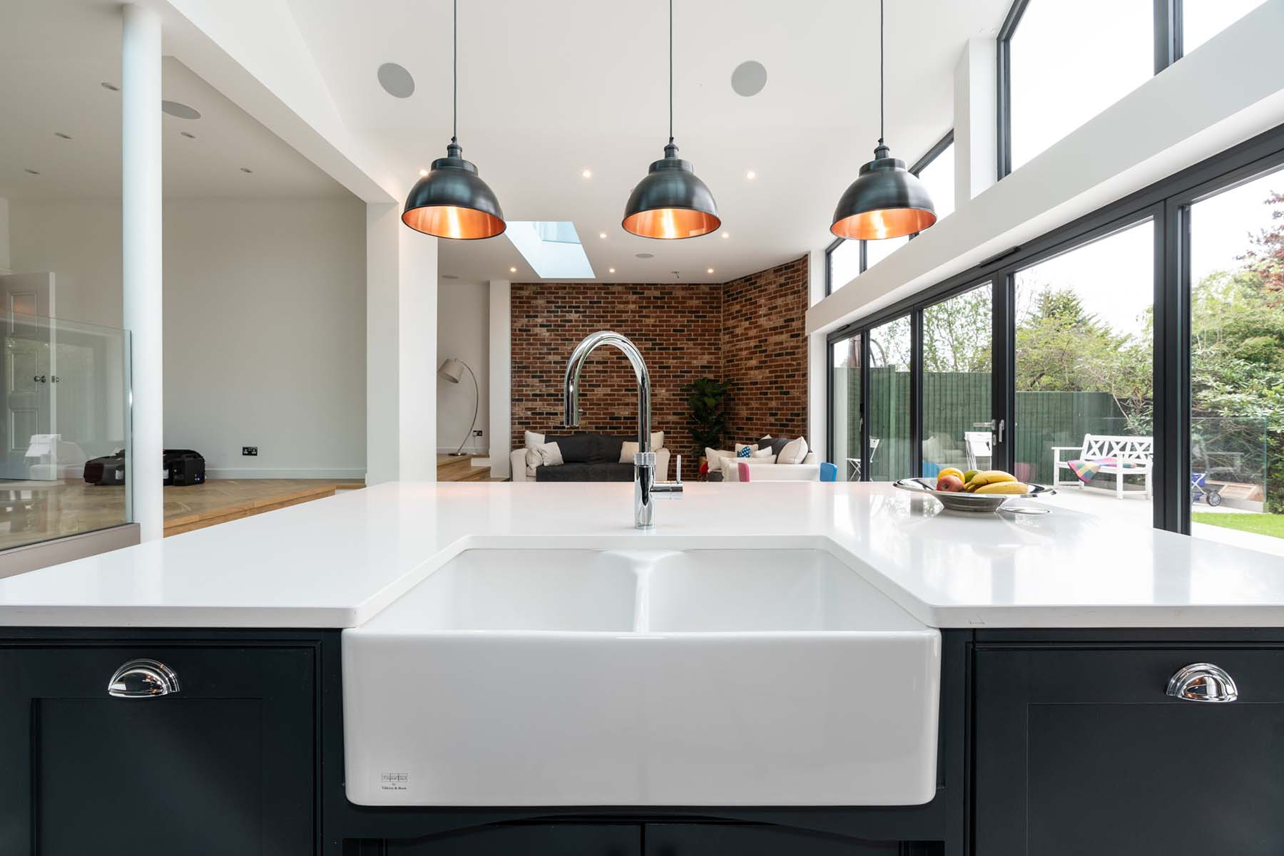 black kitchen cabinets with white countertops high ceilings huge windows red brick wall