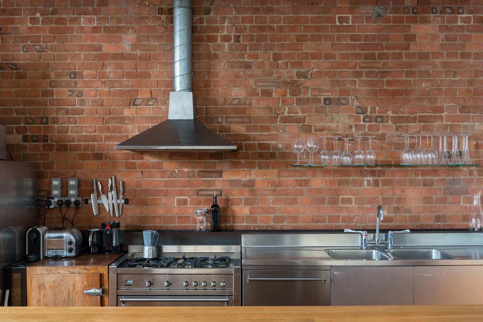 red brick kitchen with stainless steel appliances and steel countertop wood cabinets