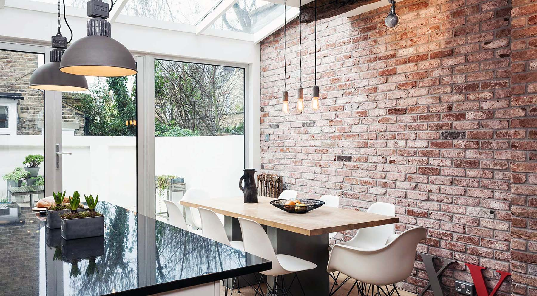 brick accent wall in the kitchen with folding patio doors and skylights