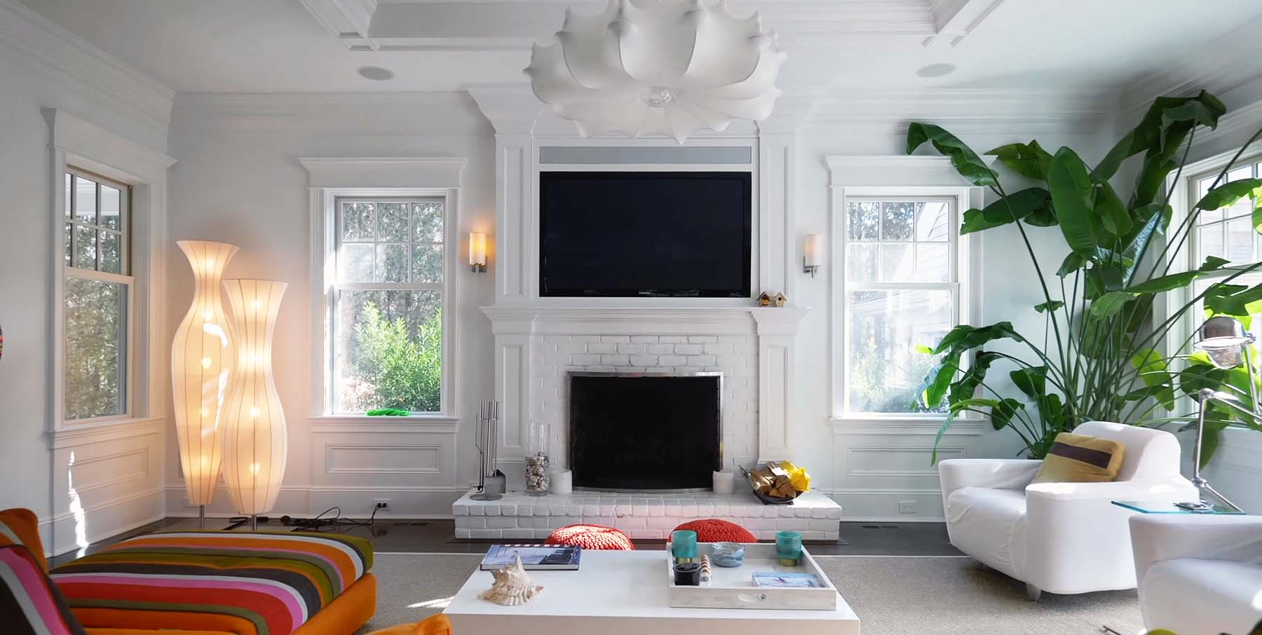painted white brick fireplace surround with wall paneling crwon molding and fireplace TV