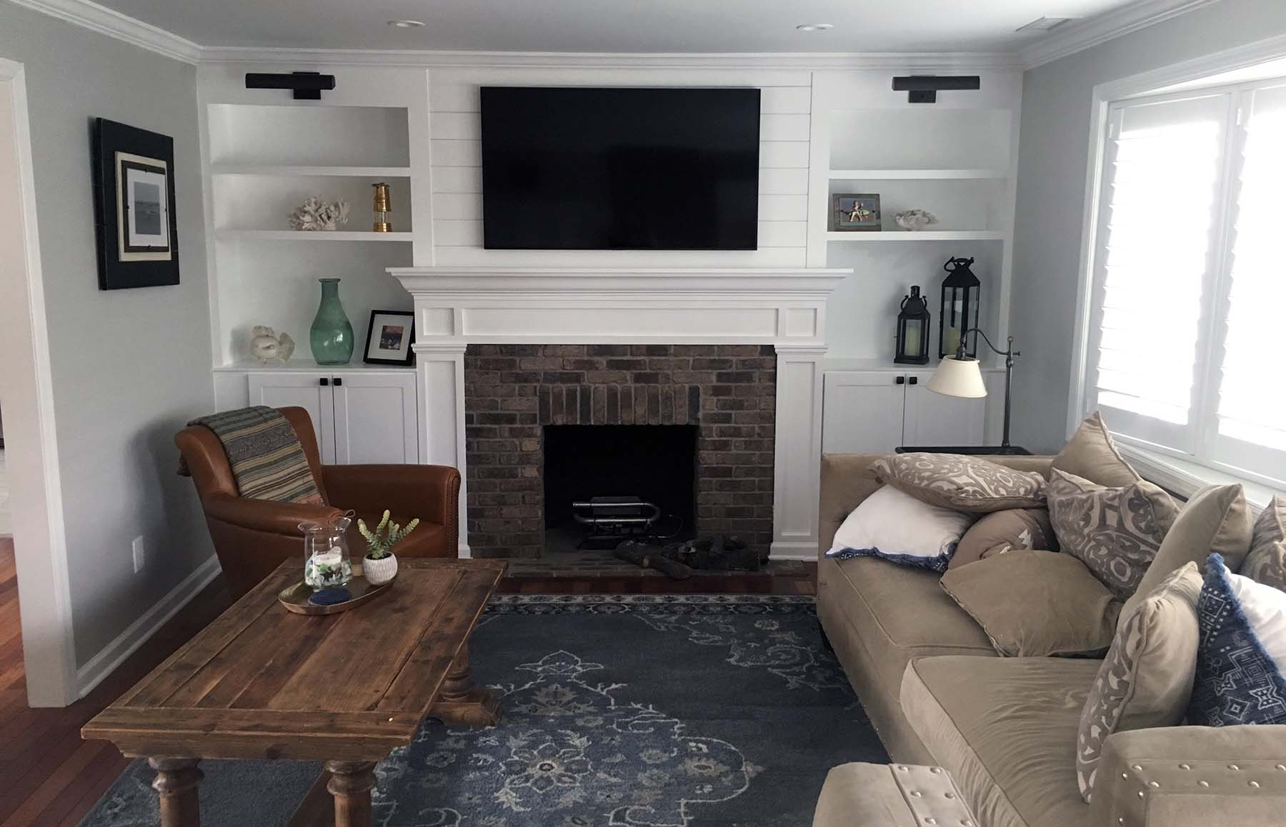 built in shelves around a faux brick fireplace surround with shiplap above fireplace mounted TV