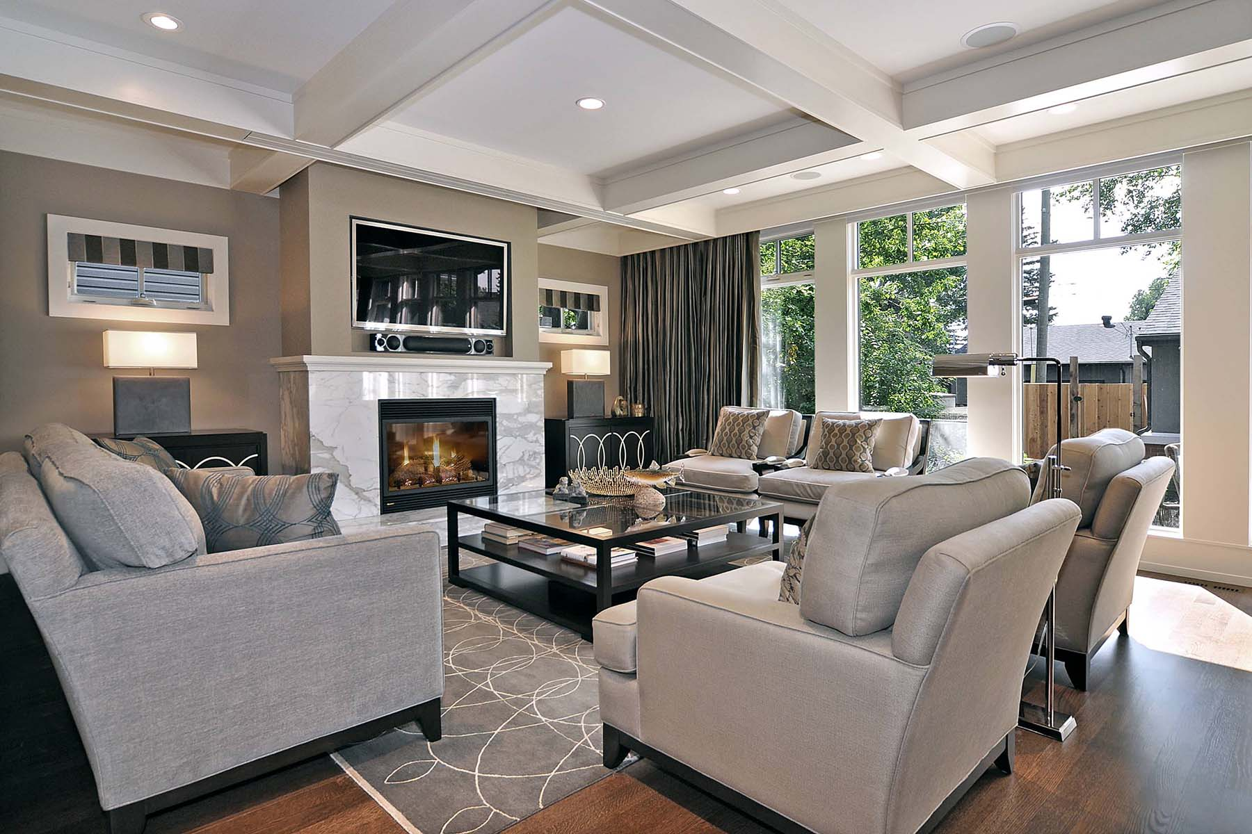 Beautiful living room with tan walls and white trim with marble fireplace surround and white coffered ceiling.