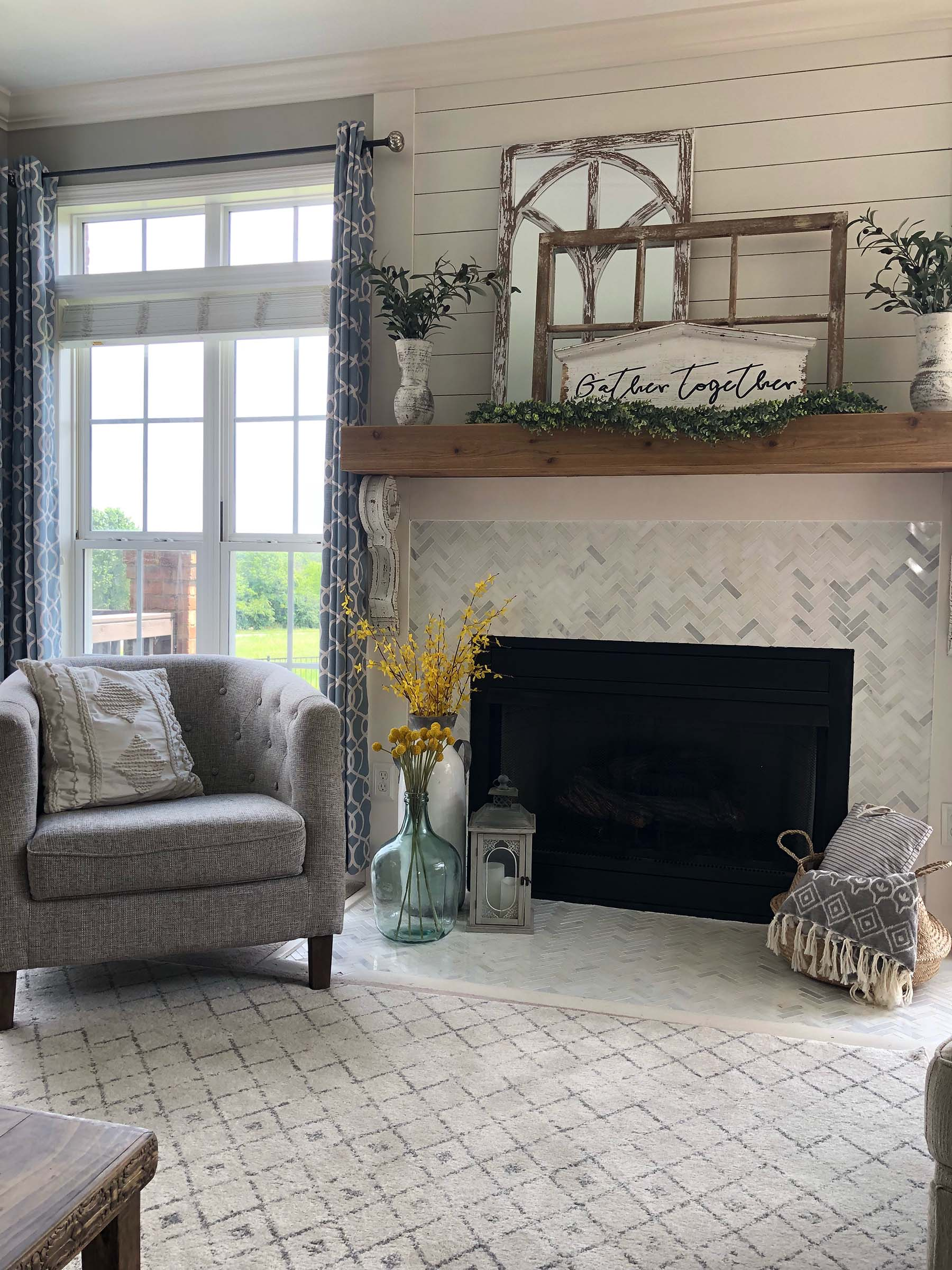 fireplace with small marble tile surround wood mantel shelf and shiplap wall paneling