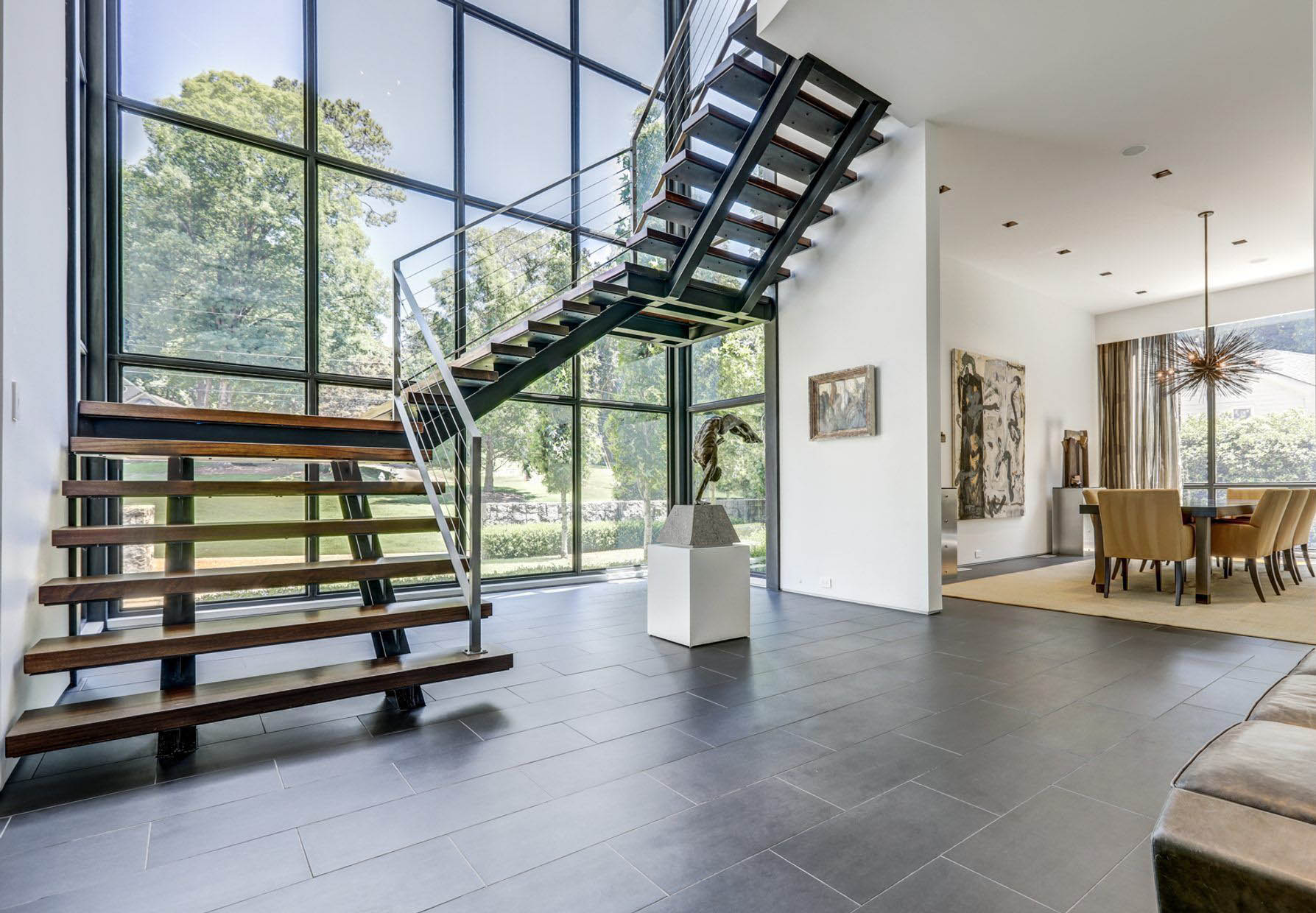Modern metal and wood winding staircase with metal railings in front of a stunning 2 story glass wall.
