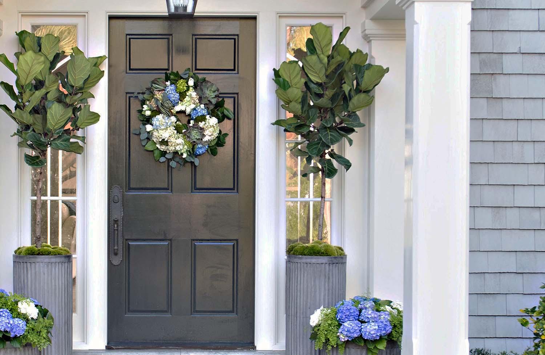 black front door with gray cedar shake siding