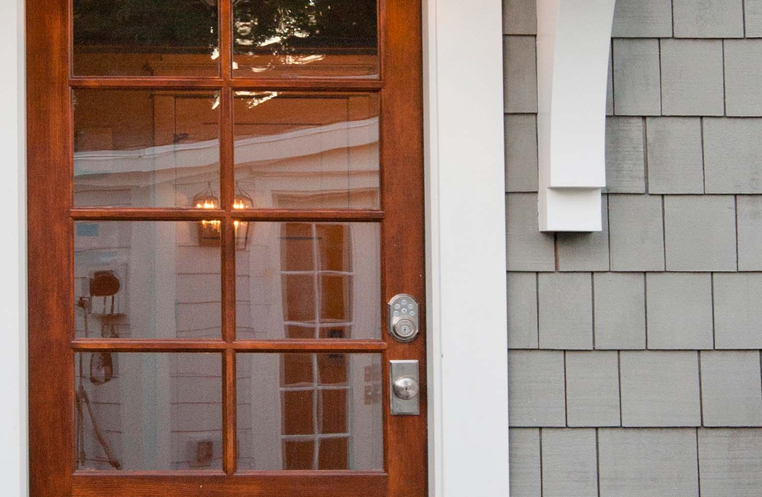 real wood front door with gray shake siding and white trim