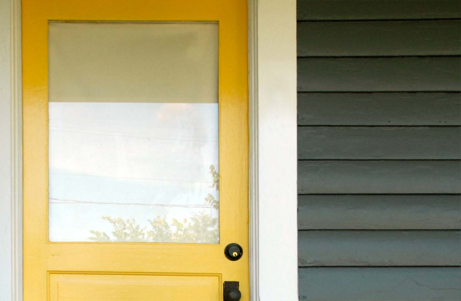 gray siding with a canary yellow front door and white trim