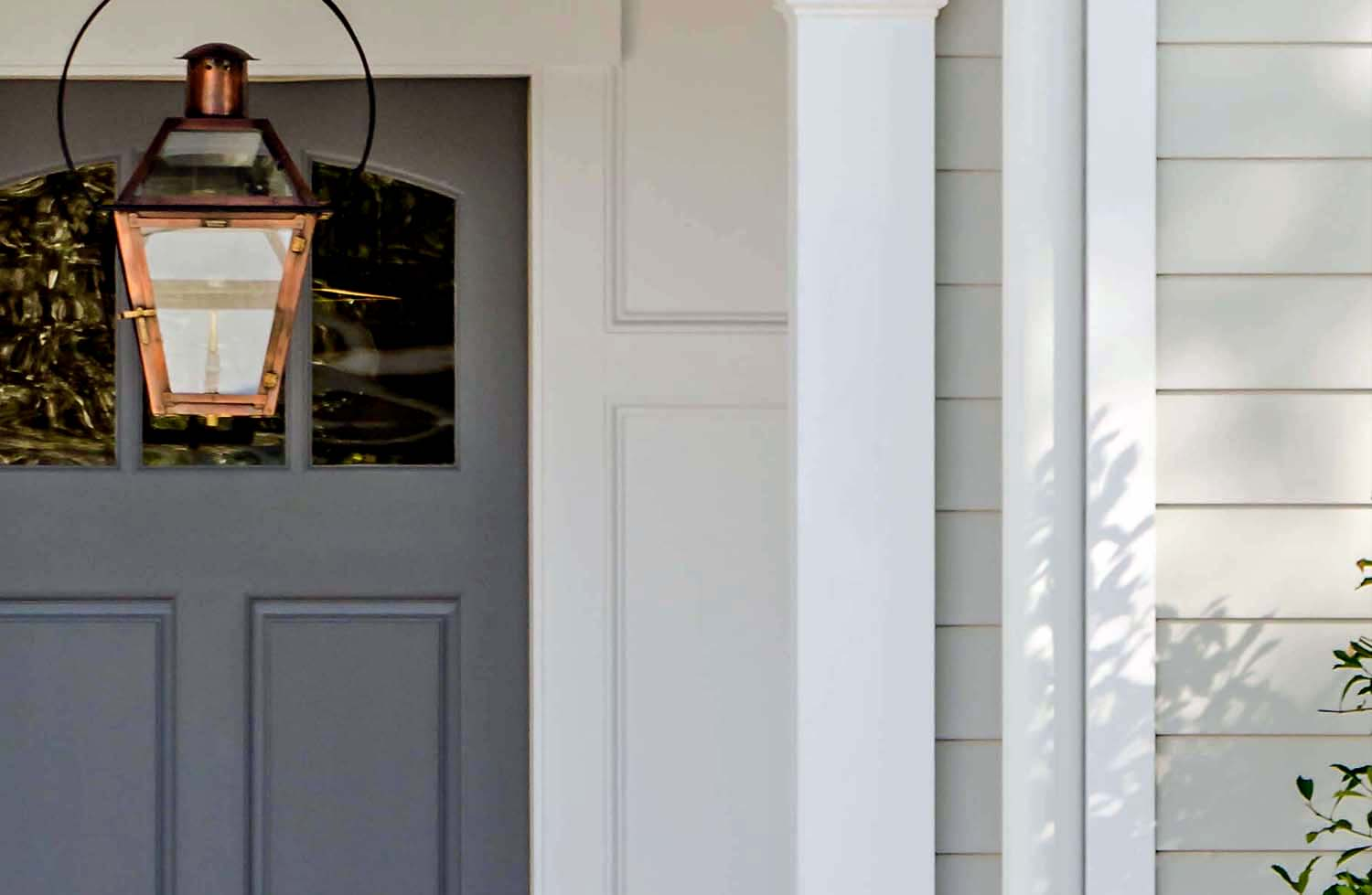 gray front door with light gray siding and brass hanging porch light